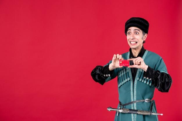 Portrait d'un homme azéri en costume traditionnel tenant une carte de crédit studio shot rouge ethnique novruz printemps argent couleurs