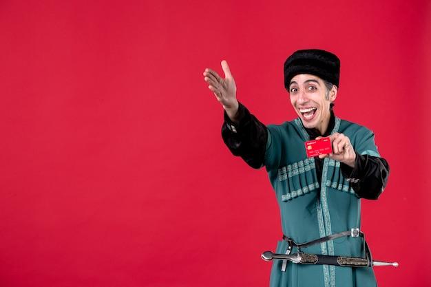 Portrait d'un homme azéri en costume traditionnel tenant une carte de crédit studio shot rouge novruz printemps argent couleur ethnique