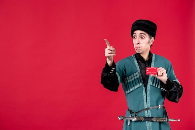 Portrait d'un homme azéri en costume traditionnel tenant une carte de crédit studio shot rouge novruz printemps argent ethnique
