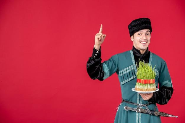 Portrait d'un homme azéri en costume traditionnel tenant le concept de printemps de semeni rouge novruz