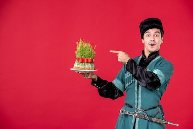Portrait d'homme azéri en costume traditionnel tenant semeni studio shot red concept danseur printemps