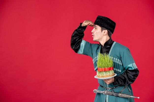 Portrait d'un homme azéri en costume traditionnel tenant un studio de semeni danseur concept rouge novruz