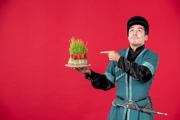 Portrait d'un homme azéri en costume traditionnel tenant un studio de semeni danseur de novruz concept rouge
