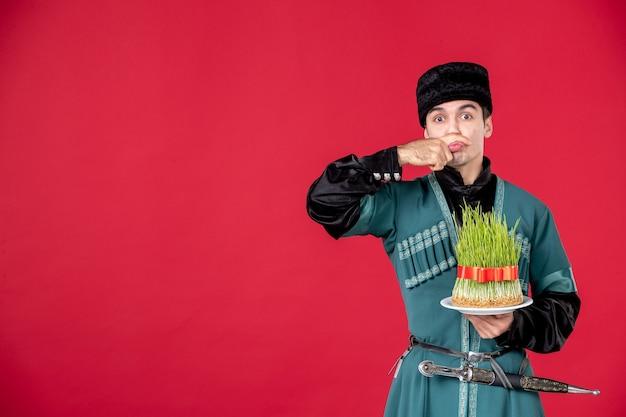 Portrait d'un homme azéri en costume traditionnel tenant un studio semeni tourné sur le printemps rouge danseur concept novruz