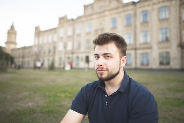 Portrait d'un homme avec une barbe à l'arrière du bâtiment universitaire.