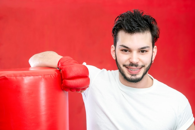Portrait d'homme avec barbe boxer en formation sur un sac de boxe dans un gymnase