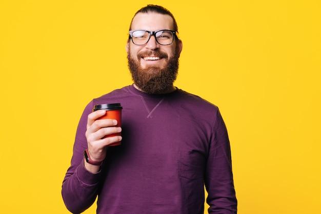 Portrait d'un homme avec barbe et lunettes qui tient une tasse de boisson chaude sourit