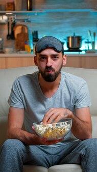 Portrait d'homme à la barbe tenant un bol de pop-corn
