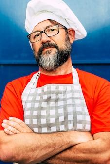 Portrait d'homme barbu adulte chef hipster à la recherche de l'appareil photo et porter le concept de chapeau blanc de restaurant ou café et les personnes qui y travaillent des lunettes et des couleurs bleu rouge photo