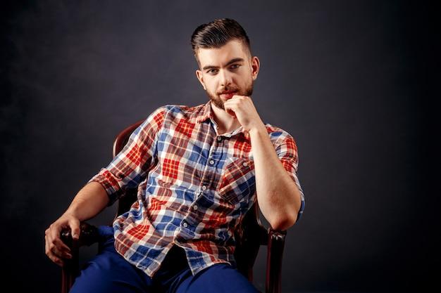 Portrait d'homme barbu aux cheveux longs sur fond sombre.