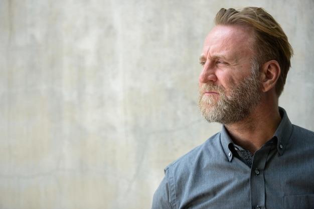 Portrait d'homme barbu beau mature avec des tatouages à la main contre le mur de béton à l'extérieur