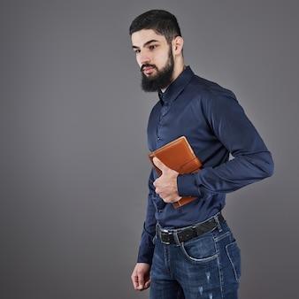 Portrait d'homme barbu beau à pleines dents avec livre sur les mains
