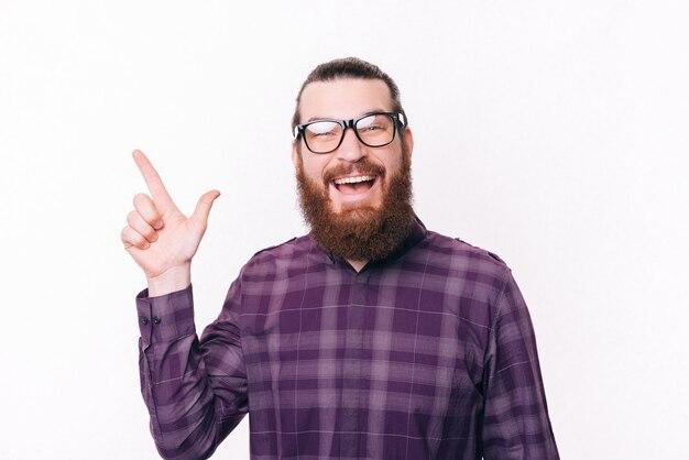 Portrait d'homme barbu en chemise portant des lunettes et pointant vers le coin