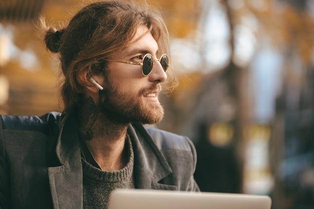 Portrait d'un homme barbu confiant dans les écouteurs