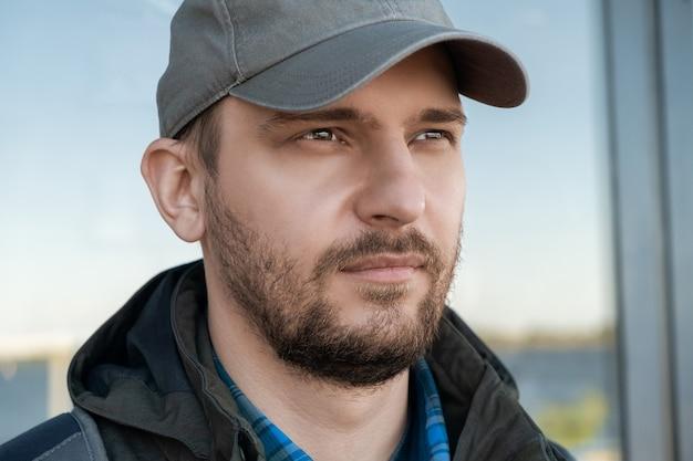 Portrait d'un homme barbu confiant sérieux dans une casquette de baseball à la recherche au loin