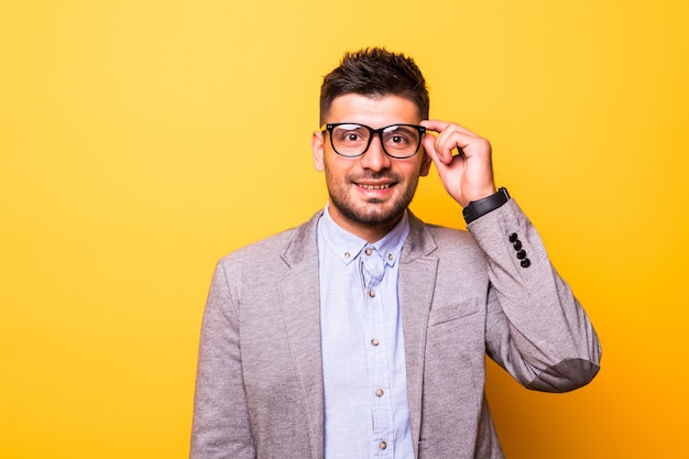 Portrait d'homme barbu dans des verres avec une expression sérieuse sur fond jaune