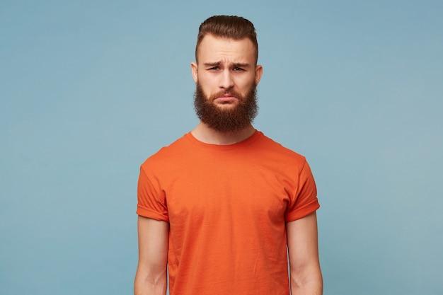 Portrait d'homme barbu émotionnel avec une expression triste sur le visage, la lèvre inférieure tordue avec un regard mécontent.