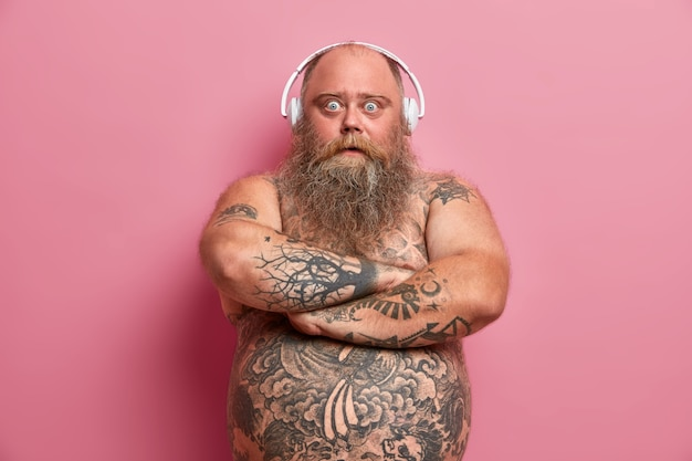 Portrait d'homme barbu étonné garde les bras croisés, regarde avec les yeux écarquillés, achète des écouteurs en soldes de vacances, attrape des ondes positives, a le ventre tatoué nu, obèse à cause d'un mode de vie paresseux