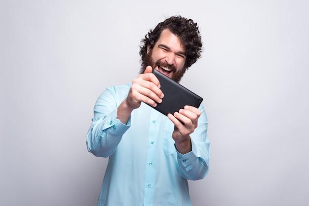 Portrait d'homme barbu étonné regardant tablette et célébrant sur blanc.