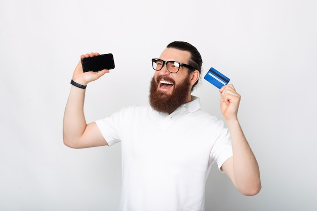 Portrait d'un homme barbu excité tenant un smartphone et une carte de crédit bleue