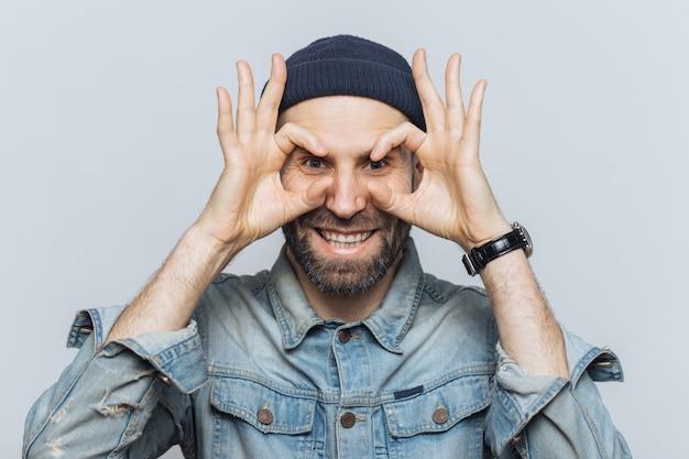 Portrait d'un homme barbu fait des lunettes avec les doigts, a la chaume, porte des vêtements en jeans