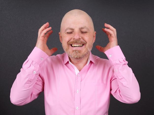 Portrait d'un homme barbu heureux dans une chemise avec les bras levés