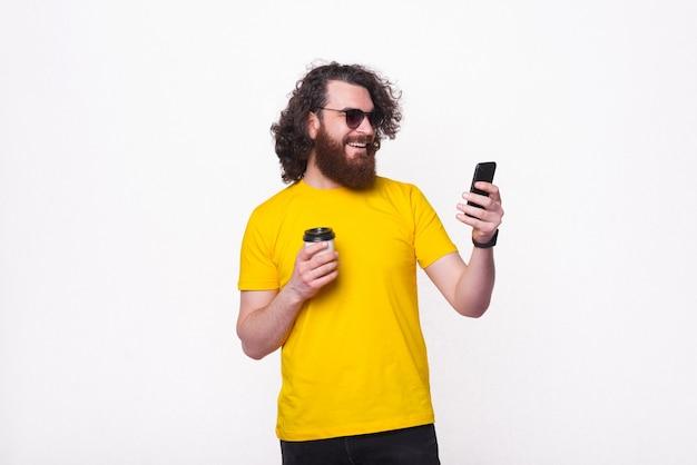 Portrait d'homme barbu hipster avec de longs cheveux bouclés boire une tasse de café à emporter et à l'aide de smartphone