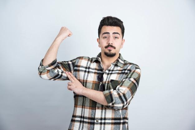 Portrait d'homme barbu avec des lunettes montrant ses muscles sur un mur blanc.