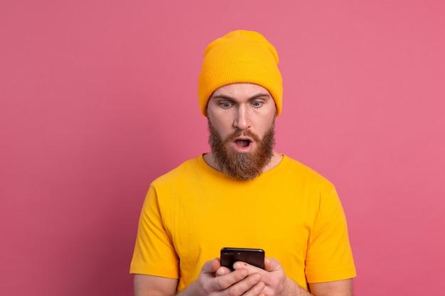 Portrait d'homme barbu mature choqué concerné haletant malheureux holding smartphone lecture message étrange et inquiétant sur rose