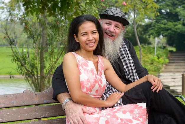 Portrait d'homme barbu mature et femme asiatique mature en couple marié