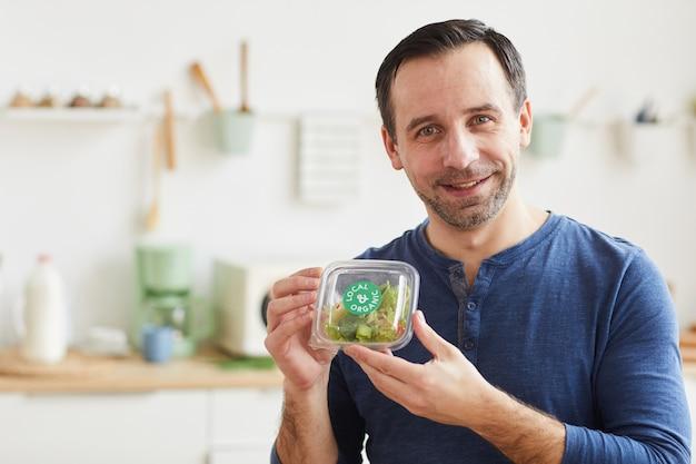 Portrait d'homme barbu mature tenant une boîte à salade et souriant tout en bénéficiant d'un service de livraison de nourriture
