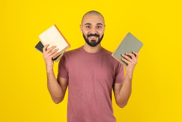 Portrait d'un homme barbu montrant la couverture du livre sur un mur jaune.