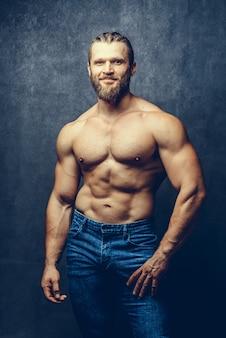 Portrait d'un homme barbu musculaire athlétique posant