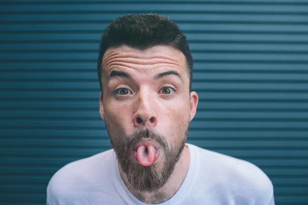 Portrait d'homme barbu regardant la caméra et hsowing sa langue. les sourcils des gars sont relevés. isolé sur rayé