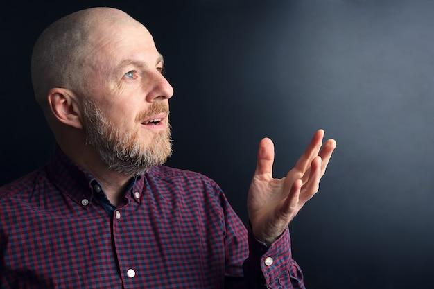 Portrait d'un homme barbu avec sa main levée vers la lumière