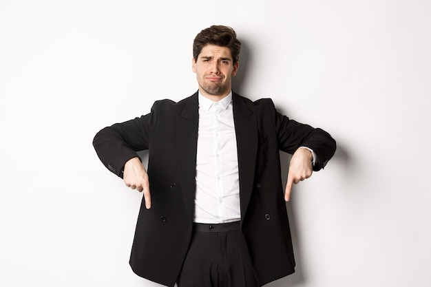 Portrait d'un homme barbu sceptique et non amusé, pointant les doigts vers le bas avec un visage déçu, debout en costume et se plaignant