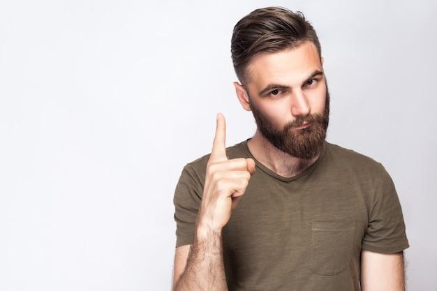 Portrait d'un homme barbu sérieux avec un doigt d'avertissement et un t-shirt vert foncé sur fond gris clair. tourné en studio. .