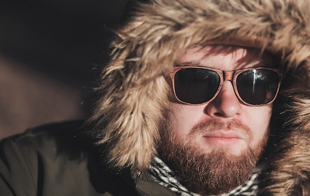 Portrait d'un homme barbu sérieux portant une veste et des lunettes de soleil en alaska d'hiver