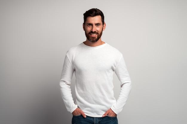 Portrait d'un homme barbu souriant heureux avec une chemise blanche sur fond gris clair et souriant à la caméra. prise de vue en studio. concept d'émotions de personnes