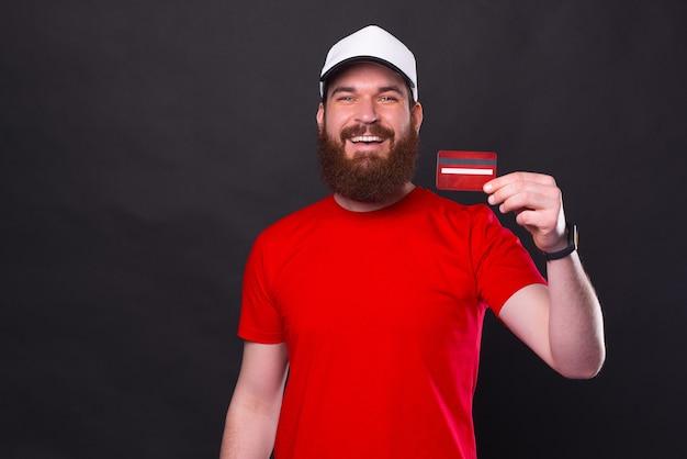 Portrait d'homme barbu souriant montrant sa nouvelle carte de crédit rouge sur fond noir