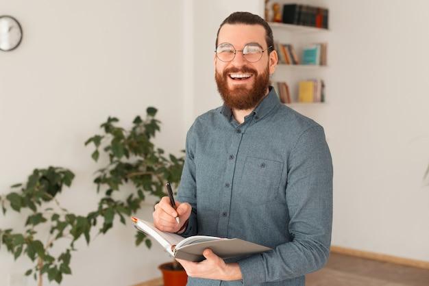 Portrait d'homme barbu souriant planification de temps au bureau