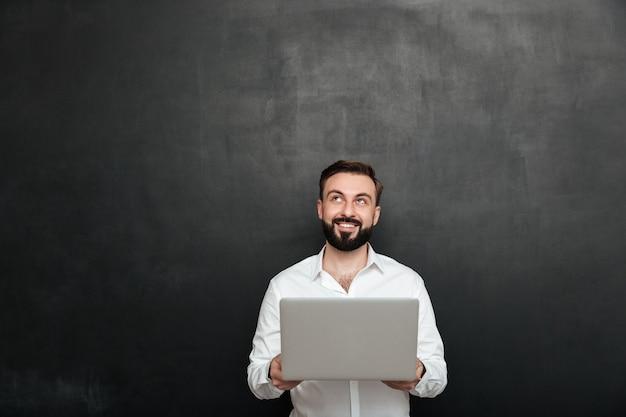Portrait d'homme barbu souriant tenant un ordinateur personnel argenté et regardant vers le haut, isolé sur un mur gris foncé