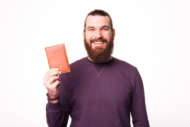 Un portrait d'un homme barbu souriant et tenant un passeport