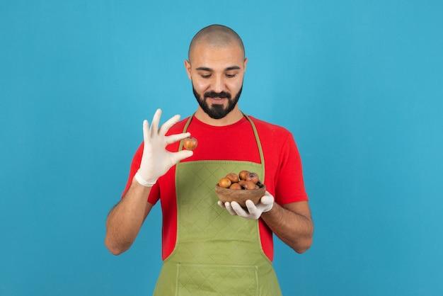 Portrait d'un homme barbu en tablier tenant un bol en bois de fruits secs.