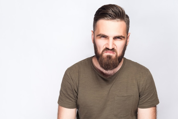 Portrait d'un homme barbu triste en colère avec un t-shirt vert foncé sur fond gris clair. tourné en studio. .