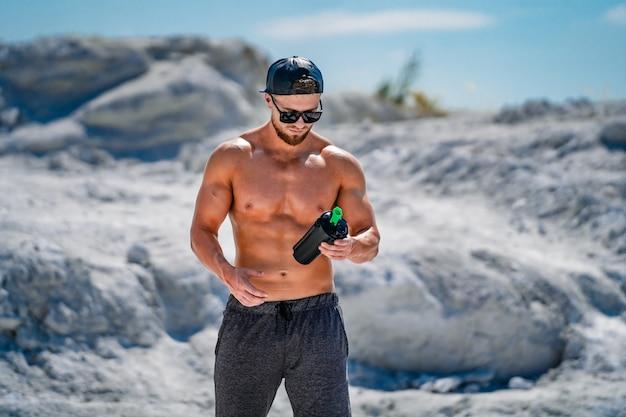 Portrait d'un homme beau bodybuilder à moitié grignoté dans des verres et une casquette avec une bouteille d'eau.