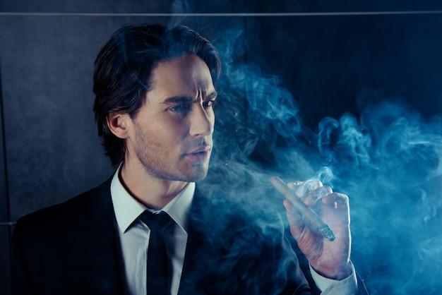 Portrait d'un homme beau brutal pense et fume un cigare
