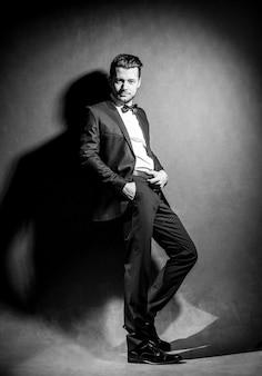 Portrait d'un homme beau confiant en costume noir avec noeud papillon posant dans un mur de studio sombre