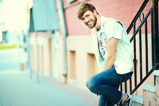 Portrait d'un homme beau dans des vêtements élégants hipster. guy attrayant posant dans la rue
