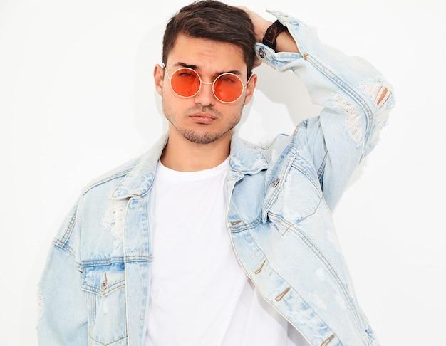 Portrait d'un homme beau jeune mannequin habillé en vêtements jeans en posant des lunettes de soleil. isolé